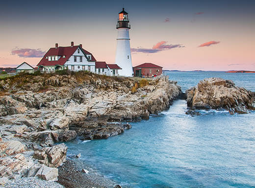 A lighthouse in Portland, Maine, sits on the edge of a rocky coastline as the sun sets.