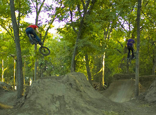Two youths on dirt bikes are seen flying in the air off of dirt ramps with leafy green trees surrounding them at Duncan Park in Austin, Texas