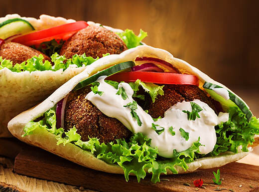 Falafel Sandwich Stuffed With Lettuce Tomatoes Cuber And White Tzatziki Sauce In Pita