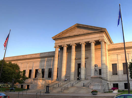 Front view of the Minneapolis Institute of Art, an ivory, stately building with columns in the front, washed in the early evening sun at dusk in Minneapolis