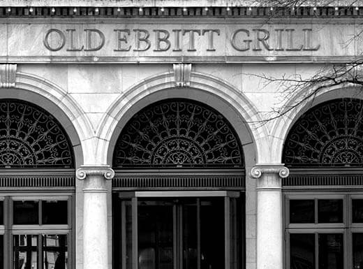A black and white image of the exterior of the Old Ebbitt Grill in Washington, D.C. on a winter day