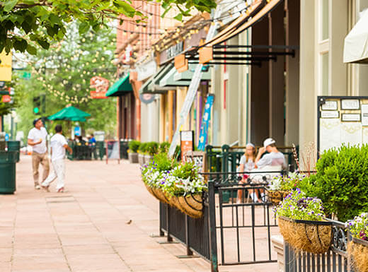 View of a sidewalk in Larimer Square in Denver during a warm day shows visitors walking and sitting on restaurant patios shaded by umbrellas
