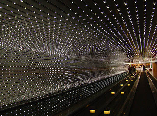 Visitors stand on moving walkways while gazing up at hundreds of dots of lights lining the dark walls and ceilings of the Multiverse light sculpture at the National Gallery of Art in Washington, D.C.