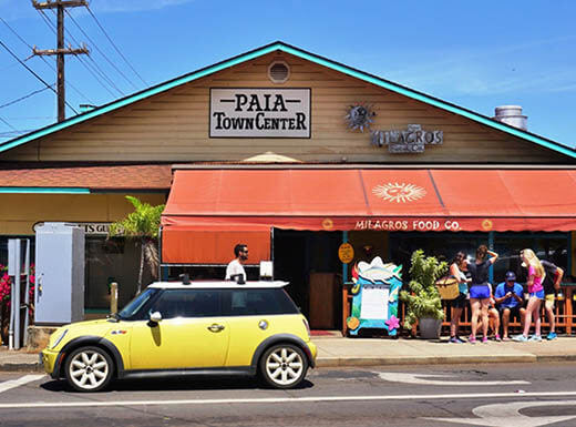 View of a street in Paia, Hawaii featuring the Town Center busy with visitors with a red awning during the daytime behind a bight yellow Mini Cooper with a bright blue sky