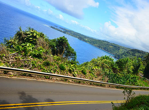 View of the winding oceanside road to Hana, Hawaii, on a clear sunny day with the ocean shore right in the backgrou