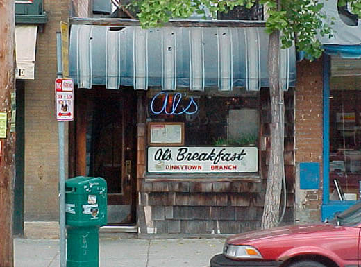 The tiny exterior of Al's Breakfast is pictured from the street in Minneapolis, Minnesota, with its faded blue and white awning and old neon sign reading Als
