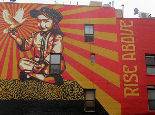 A red and yellow mural on an apartment wall in New York that reads rise above