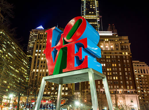 The famous red and blue Love statue is well-lit at night in the Love Park located in Philly with skyscrapers illuminated in the background
