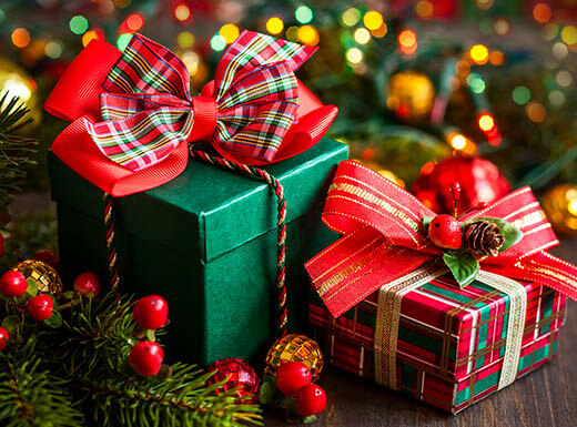 Two holiday gifts are pictured under a tree, with greenery, berries, and lights in the background.