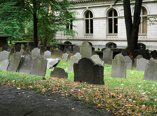 A view of one of the oldest graveyards in the United States, King's Chapel Cemetery in Boston, Massachusetts on a fall day shows leaves scattered along a dirt path next to tombstones with a church in the background