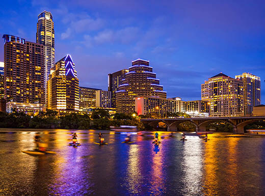 The Austin, Texas skyline is pictured at night, with its bright downtown lights reflecting off Lady Bird Lake in the foreground.