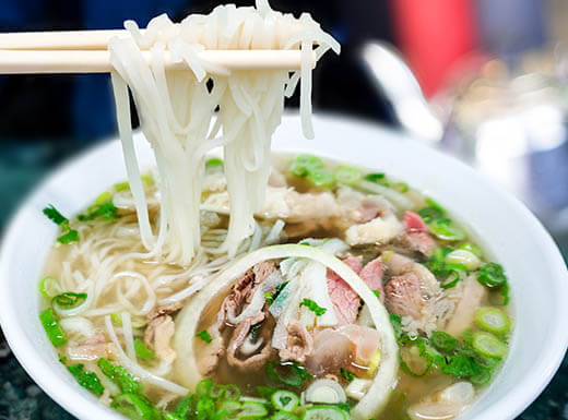 Lunchtime bowl of Vietnamese beef noodle soup, or pho with onions, green onions and other toppings  in a white bowl chopsticks pulling out rice noodles at a restaurant in Little Saigon in San Jose, California