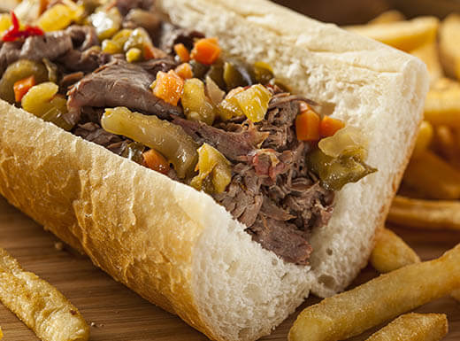 A close up view of a hearty Italian beef sandwich with French fries, served in a restaurant in Chicago, IL