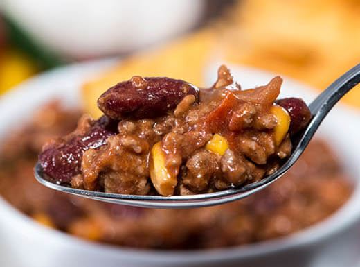 A spoonful of chili is pictured in front of a white bowl of chili at Ben's Chili Bowl in Washington, D.C.
