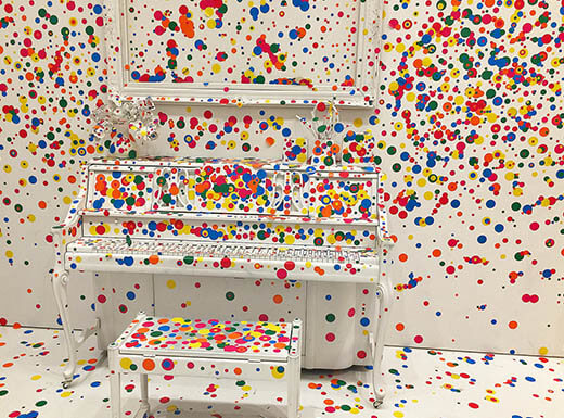 'Piano, Stool, and Picture in the Obliteration Room' as seen in the Kusama Exhibit at the Hirshhorn Museum in Washington, D.C. shows white walls and floor with white furniture and décor, all covered in red, blue, yellow and green dots