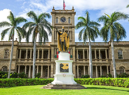The King Kamehameha statue is pictured in front of Aliiolani Hale, the current home of the Hawaii State Supreme Court, with palm trees on either side in Honolulu, Hawaii