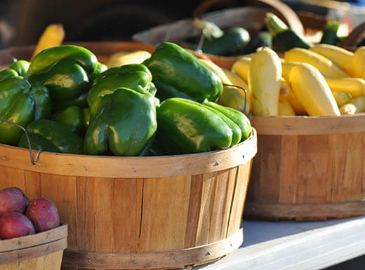 Red potatoes, green bell peppers and yellow squash are pictured in three different wood baskets on a table at the State Farmers Market at City Market in Raleigh, North Carolina