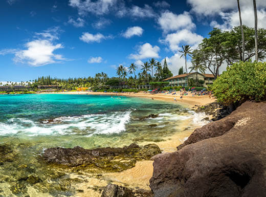 View of Napili Beach on Maui, Hawaii, with rocks extending into the turquoise ocean water and a view looking down the beach under a bright blue sky, lined with palm trees