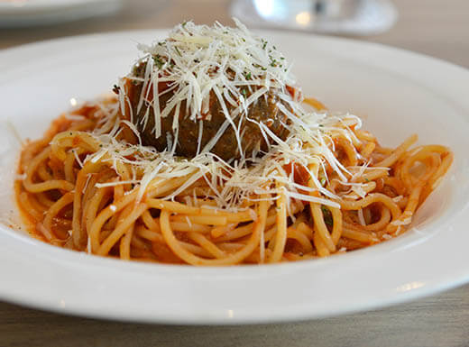 Bowl of spaghetti with the Sunday Night meatball, with grated parmesan cheese on top sit on a white plate at The Bizzarro Italian Café in Seattle