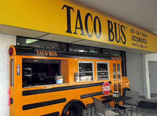 Exterior of Taco Bus restaurant , which is actually a yellow school bus, below yellow sign with black writing and table in front on Franklin Street in Tampa, Florida