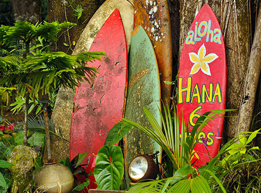 Four red, yellow and green surfboards are pictured leaned up against the side of a building on the road to Hana, surrounded by tropical greenery in Maui, Hawaii