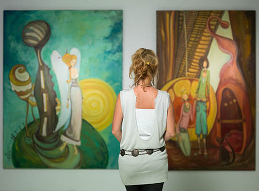 The back of a Woman wearing white is seen contemplating colorful painting in NY museum