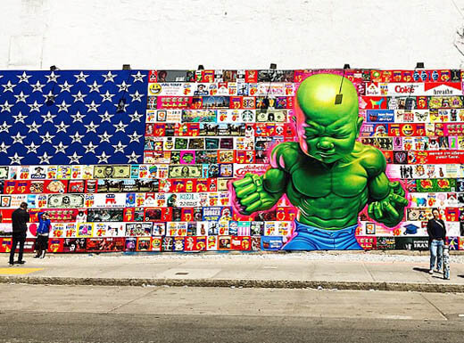 A very colorful wall art mural on the Houston Bowery Wall with the American flag dotted with cartoons all over it and a giant green Hulk-like figure busting through it in New York