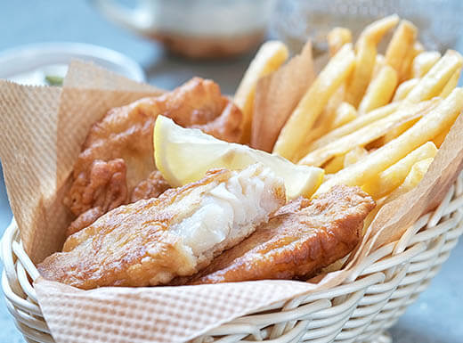 A basket of Fish and Chips (fried Cod and French fries) sits in a basket on a table with a side of tartar sauce