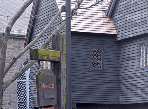 Image of the front exterior of the Salem Witch Museum in Salem, Massachusetts, a weathered, gray building on a cold winter day with an old wooden sign out front that reads 'Witch House' hanging from an old wooden post