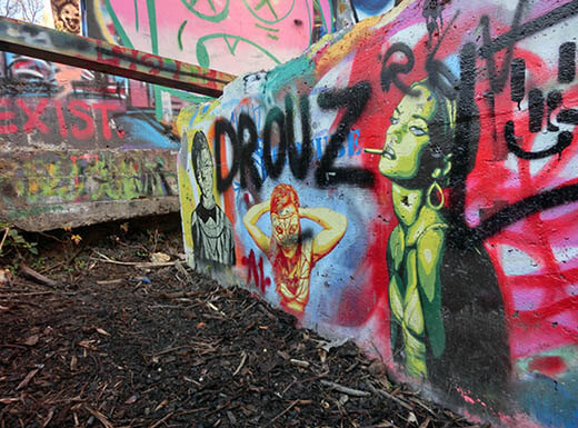 The bright colors of graffiti on a wall and dumpster are pictured at the graffiti park at HOPE Outdoor Gallery in Austin, Texas on an overcast morning.