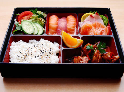 A Bento box sits on a table with white rice, sushi and vegetables at a restaurant in Los Angeles, California