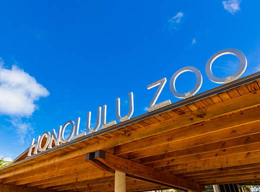 Front gate sign at the Honolulu Zoo on a bright sunny day with blue skies and white puffy clouds in the background