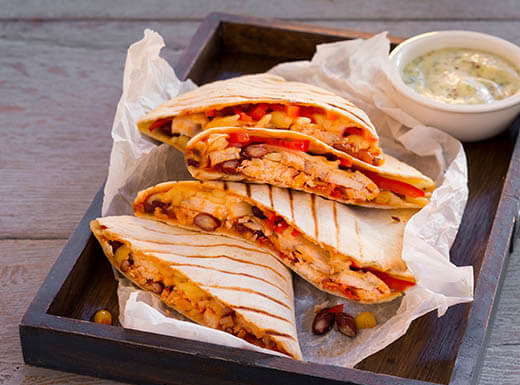 A quesadilla filled with chicken, veggies, beans, and cheese, is served on a platter with a side of creamy habanero sauce