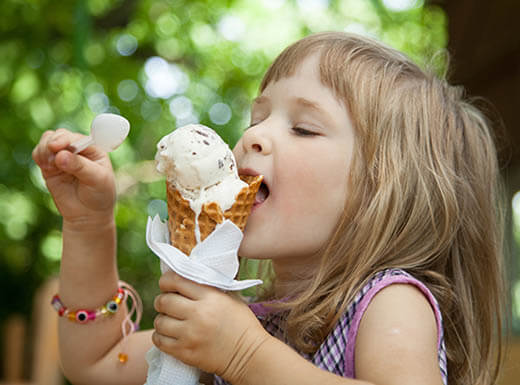 A little girl eats a large ice cream cone from Treat at the Historic City Market in Raleigh, North Carolina