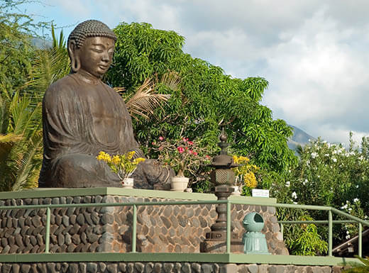 A large statue of Buddha is pictured on a stone perch with flowers surrounding it and green leafy trees in the background at the Lahaina Jodo Mission In Maui, Hawaii on a cloudy day
