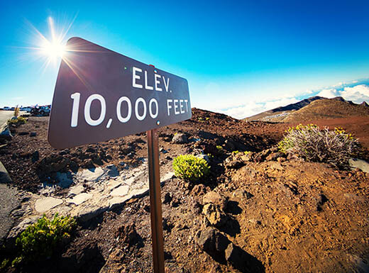 A 10,000 feet elevation sign at the summit of Haleakala in Maui, Hawaii, under clear blue sky and sun