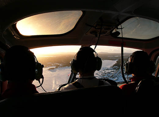 inside helicopter, pilot with 2 passengers
