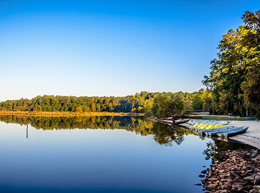 Still water reflects the clear blue afternoon sky, with a pier on the right side with canoes on it at Lake Crabtree County park just outside of Raleigh, North Carolina in early autumn