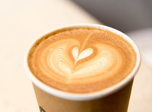 A café latte in a to-go cup, with a heart design made from foam