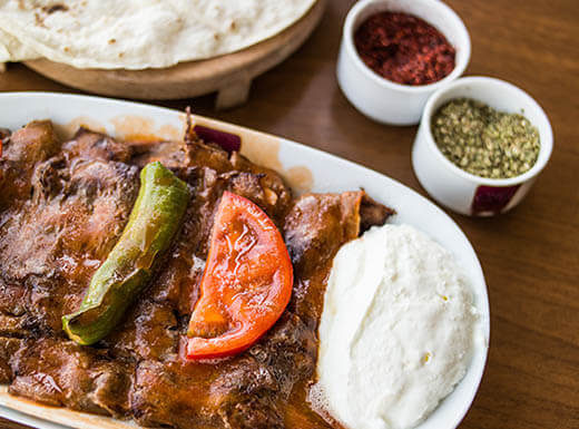 "=""A Turkish kebab with yogurt is pictured with spices and bread on the side on a wooden table at the restaurant Troy in Austin, Texas."