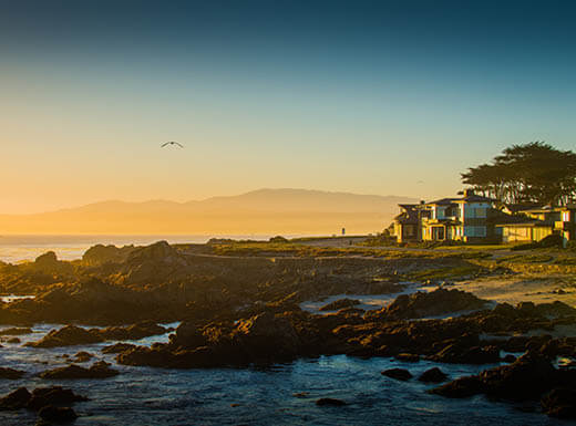 A view of a house on the stunning, rocky coastline of Monterey, California, at sunset.