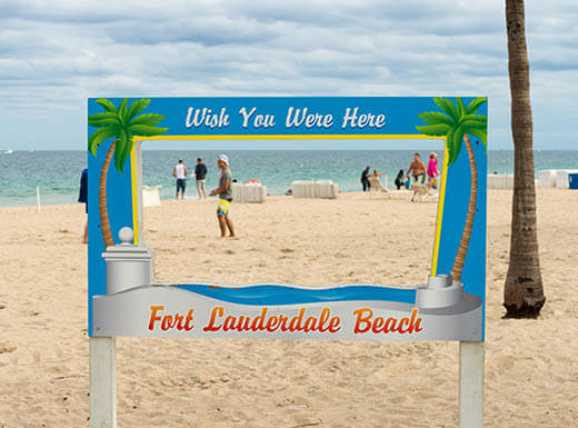 """A sign on Fort Lauderdale Beach reads """"Wish You Were Here,"""" as people can be seen walking and playing on the beach behind it"""