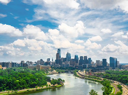 The Philadelphia skyline and river both shine under a blue sky on a gorgeous day with the river and green trees in the foreground