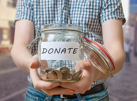 """Man in plaid shirt and jeans holding jar filled with coins and the word """"Donate"""" on it."""