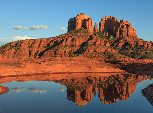 The red sandstone of Cathedral Rock in Sedona, Arizona, reaches into the sky and reflects in a body of water during a cloudless day.