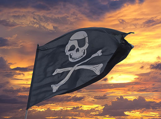 A black pirate flag with a white skull and crossbones pictured on it blows in the wind, with an orange, purple and blue sunset in a cloudy sky in the background in Fort Myers, Florida