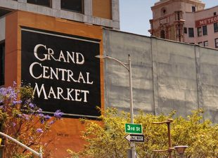 Cement buildings sit in front of a light blue sky, with a black sign reading Grand Central Market on the side of one in Los Angeles, California