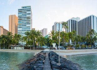 A panoramic view of a pier with large black stones on either side and water surrounding it leads to a beautiful beach with the skyline of Honolulu in the background on a beautiful day in Hawaii