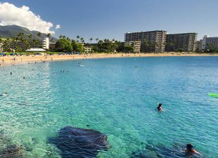 The aqua blue waters of the Pacific Ocean are pictured from Black Rock on Kaanapali Beach with the buildings of Maui, Hawaii and a bright blue sky in the background on a clear day