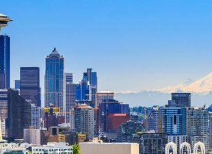 View of downtown Seattle skyline with the Space Needle and Mt Rainier in view on a sunny day